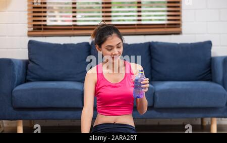 La jeune femme asiatique prend un repos après l'entraînement et boire de l'eau après l'entraînement dans le salon