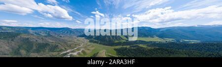 Vue panoramique panoramique panoramique sur une bannière d'un col Chike-Taman dans les montagnes de l'Altaï avec des arbres verts, le ciel bleu et des nuages. Banque D'Images