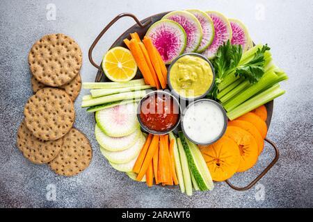 Bol Bouddha de matières mixtes avec des sauces de légumes en-cas. Les carottes, concombres, kaki, le céleri et radis, haut Vue, télévision lay Banque D'Images
