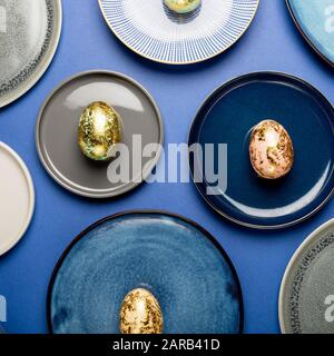 Plaques en céramique avec différents mouchetée d'or les oeufs de Pâques des tons pastels sur fond bleu. Happy Easter concept, design minimaliste, vue du dessus