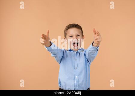 Joli petit garçon enfant dans une chemise bleue pointant vers un geste de doigt sur fond beige. Banque D'Images