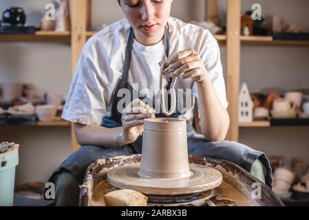 Potter travaillant sur une roue de Potter faisant un vase. Jeune femme formant l'argile avec ses mains créant pichet dans un atelier.