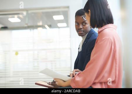 Portrait d'un homme d'affaires africain qui a réussi à parler à une collègue ou à une secrétaire en se tenant à l'intérieur du bureau, copier l'espace Banque D'Images