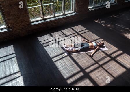 Jeune femme calme pratiquant le yoga couché dans le corps mort pose se détendre sur tapis en studio