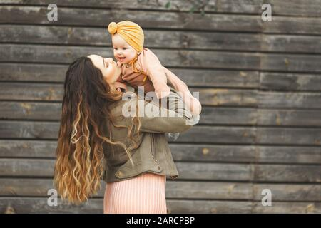 Incroyablement belle mère tenant dans ses bras sa fille et s'embrasser à l'extérieur. Look élégant à la mode. Banque D'Images
