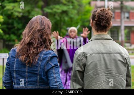 Vue arrière d'un couple portant des vestes en denim et écoutant l'histoire de conte de fées par le conteur africain contre les arbres en événement pendant le festival