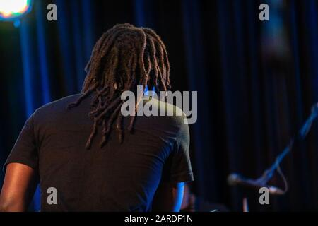 Vue arrière détaillée de l'homme portant un t-shirt noir avec des cadenas marron tout en réalisant sur scène un studio éclairé contre le rideau Banque D'Images