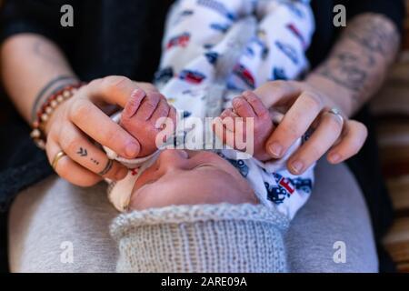 Une vue rapprochée et recadrée d'une nouvelle mère et d'un bébé garçon se liant à la maison, tenant les mains dans les jours après la naissance, beau moment de la parentalité. Copier l'espace sur les côtés