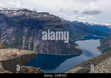 Femme Se Tenant À Bord De Cliff À Trolltunga Mountain En Norvège. Banque D'Images