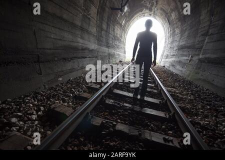 Homme silhouetted dans un tunnel debout au centre des voies ferrées regardant vers la lumière au bout du tunnel dans une image conceptuelle. Banque D'Images