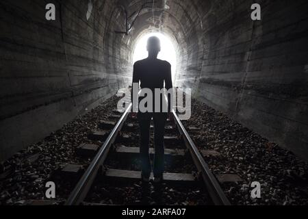Sortie de darknes - lumière au bout du tunnel, hommes dans le tunnel de train. Banque D'Images