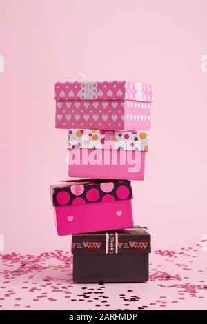 une pile de boîtes cadeaux carrées en carton sur un fond rose avec des confettis brillants, toile de fond festive. Banque D'Images