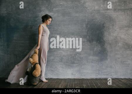 Une fille dans une robe rose Marche à côté d'un mur gris et Tient un ours en peluche dans ses Mains. Carte Postale Banque D'Images