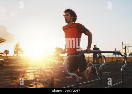 Sportif jeune athlète masculin écoutant de la musique sur des écouteurs exerçant sur des barres parallèles faisant des push-ups dans le parc - jeune homme faisant des creux à l'extérieur
