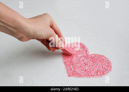 La main gauche de fille dessin coeur sur le mur blanc avec craie rose Banque D'Images