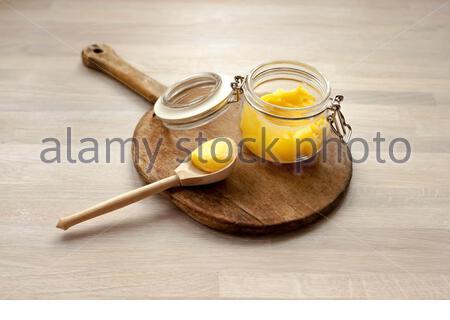Le ghee a clarifié le desi de beurre dans un pot en verre avec une cuillère faite de bois sur fond de bois naturel Banque D'Images