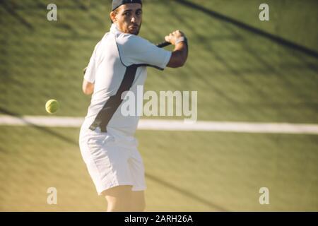 Un jeune joueur de tennis masculin frappe une main arrière puissante pendant un match. Joueur de tennis jouant au tennis sur un terrain de golf. Banque D'Images