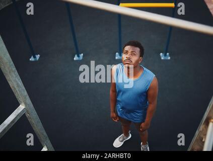 Vue en grand angle d'un jeune homme sportif qui se prépare à faire des pull-up sur un bar à la salle de gym extérieure dans le parc - copyspace