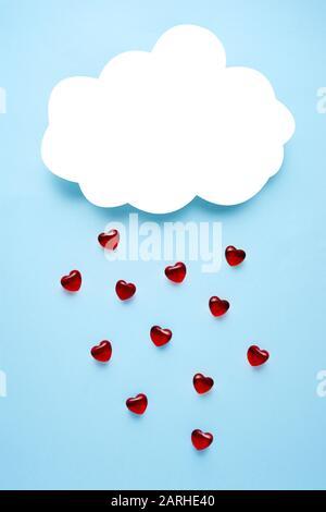 Concept créatif vacances valentines jour amour photo de papier fait main nuage pleurant avec les coeurs sur fond bleu. Banque D'Images