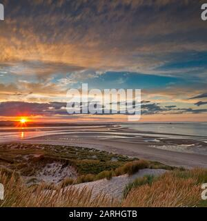 Coucher de soleil sur Budle Bay en direction de Lindisfarne près de Bamburgh, Northumberland, Angleterre, Royaume-Uni Banque D'Images