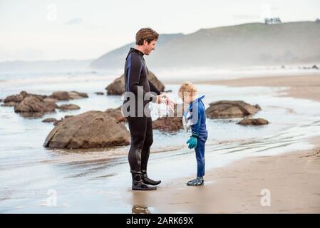 Père et fils en combinaisons sur la plage en Nouvelle-Zélande Banque D'Images
