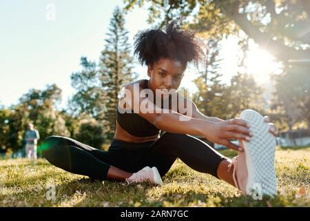 Portrait d'une jeune femme afro-américaine déterminée assise sur l'herbe verte le matin lumière du soleil étirant ses jambes regardant l'appareil photo