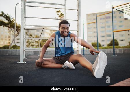Portrait d'un coureur souriant assis sur un parc de salle de sport extérieur qui étire les jambes pour se préparer à l'entraînement de course