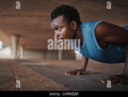 Jeune homme sportif américain africain qui fait des poules sur le pavé à l'extérieur