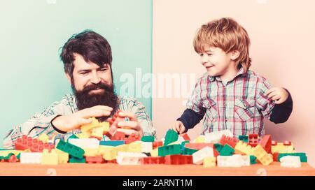 Famille est mieux. petit garçon avec papa jouant ensemble. happy family loisirs. père et fils jouer jeu. immeuble accueil aux couleurs constructeur. le développement de l'enfant. L'évolution des responsabilités. Banque D'Images