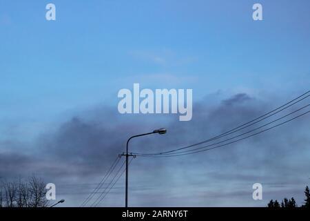 Fumée noire dans le ciel bleu du soir Banque D'Images