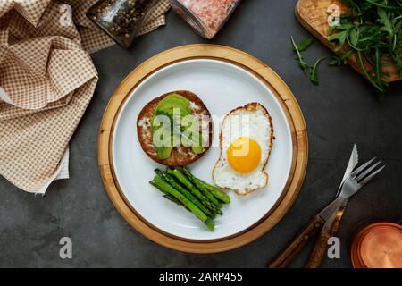 Sandwich grillé à l'avocat et un œuf frit sur une plaque blanche avec asperges. Nourriture ou petit déjeuner sains. Fond sombre. Banque D'Images