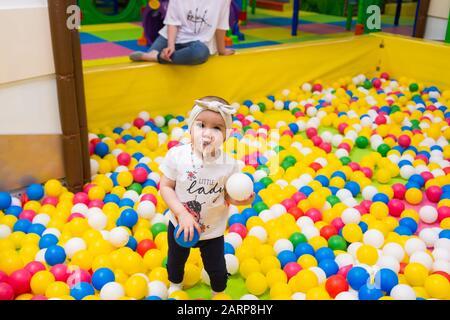 une jolie petite fille jouant dans l'aire de jeux intérieure dans un centre commercial. Banque D'Images