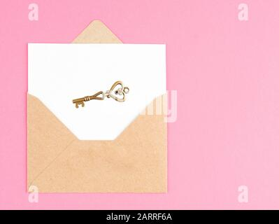 Enveloppe Kraft avec une feuille blanche et une touche ancienne sur un fond rose Banque D'Images