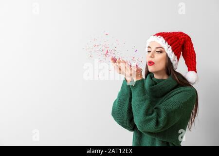 Belle jeune femme à Santa Hat et avec confetti sur fond clair Banque D'Images