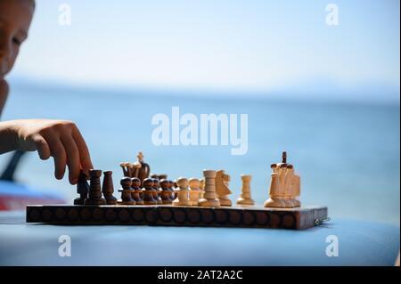 Petit garçon jouant aux échecs sur sup board sur la plage avec l'océan en arrière-plan. Banque D'Images