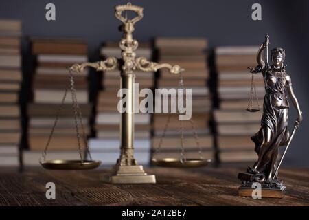 Thème de la loi. Statue de THEMIS, pèse-personnes et livres juridiques sur table en bois rustique. Banque D'Images
