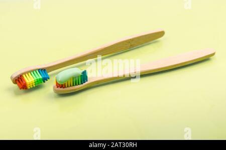 Brosse à dents en bambou avec dentifrice écologique sur fond pastel. Paire de brosses à dents en bois multicolores