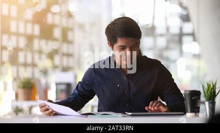 Un jeune employé de bureau intelligent qui se concentre sur son travail et utilise une tablette informatique au bureau moderne.