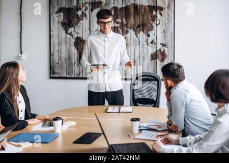 Jeune homme séduisant en lunettes avec une tablette entre ses mains présente son projet lors d'une réunion Banque D'Images