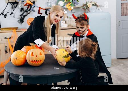 Mère et enfants s'appuyant sur la citrouille, jouer et avoir le temps drôle à la maison. -concept d'Halloween