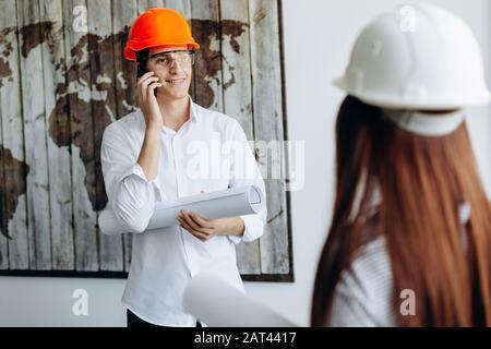 Beau jeune homme d'affaires réussi dans le casque orange tire et parle sur le téléphone mobile