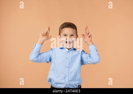 drôle petit garçon enfant en chemise bleue faisant un geste de pistolet sur fond beige. Banque D'Images