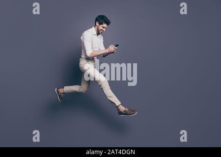 Photo pleine longueur d'un gars gai recevez le message de la petite amie lire sms de smartphone profitez de la date de saut porter chemise blanche tenue isolée sur gris