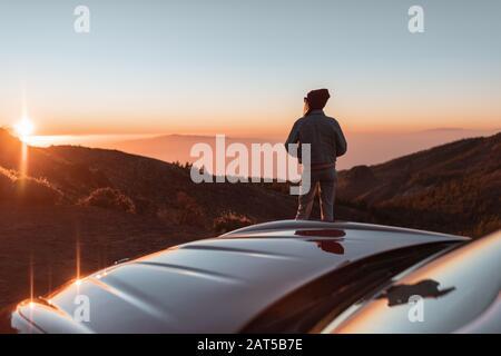 Vue sur le paysage au bord de la route au-dessus des nuages avec une femme profitant d'un beau coucher de soleil tout en voyageant sur la voiture de sport convertible Banque D'Images