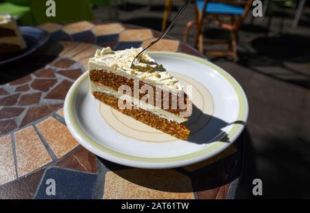 Délicieux gâteau aux carottes avec une fourchette coincée dans, servi sur une plaque dans un café le jour ensoleillé.