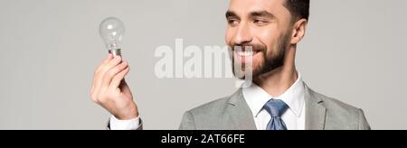 photo panoramique d'un homme d'affaires souriant tenant une ampoule isolée sur gris