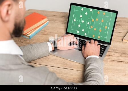 vue courte des hommes d'affaires jouant au jeu vidéo de football sur ordinateur portable isolé sur gris