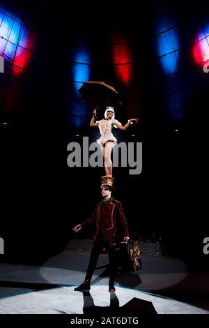 magnifique gymnast avec parapluie en spectacle tout en se tenant sur le chapeau de l'homme dans le cirque Banque D'Images