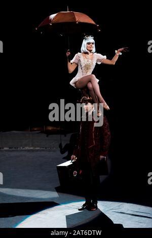 jolie femme avec parapluie en spectacle tout en s'asseyant sur un chapeau d'homme dans le cirque Banque D'Images