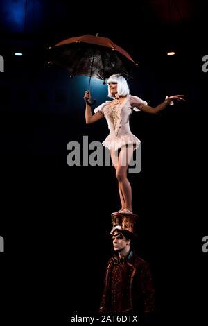 jolie femme avec parapluie en spectacle tout en se tenant sur le chapeau de l'homme dans le cirque Banque D'Images